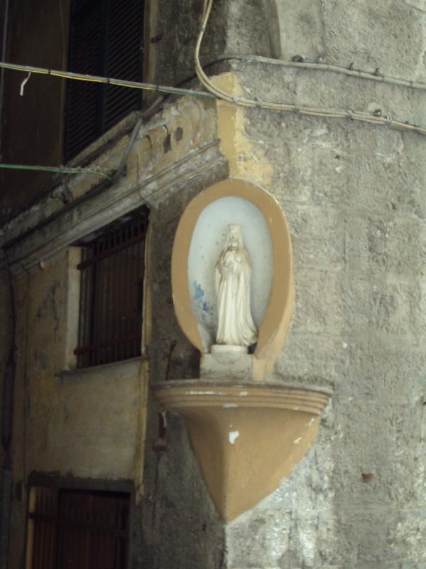 Мария поближе. На углах домов устанавливать какие-либо скульптуры — это от римлян, конечно. Они себе много чего тоже вешали на углы, включая фалосы для богатства.